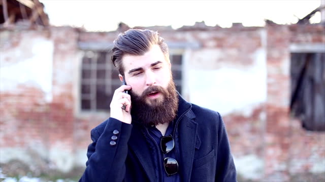 Handsome hipster with beard talking on mobile phone
