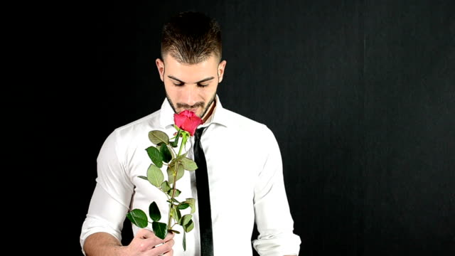 Handsome man giving a red rose