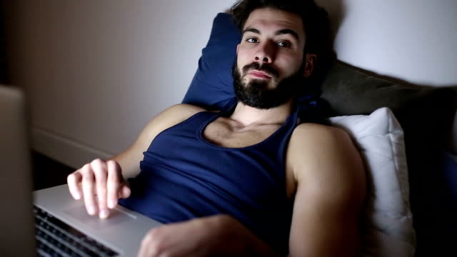 Gut aussehender Mann auf der Suche nach etwas Unterhaltung im Internet, bevor Sie Sleeep