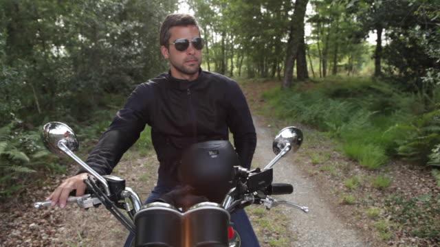 Handsome man riding motorcycle on backroads in rural landscape