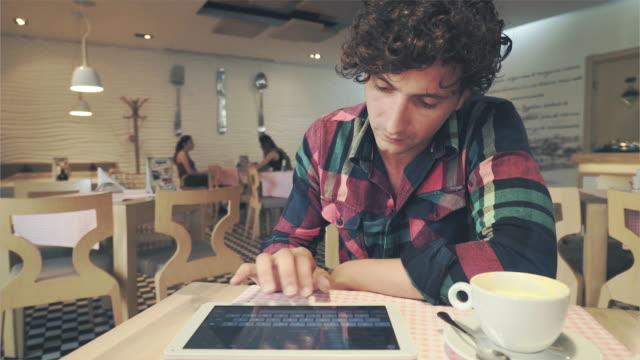 Knappe man met behulp van digitale tablet in een koffieshop.