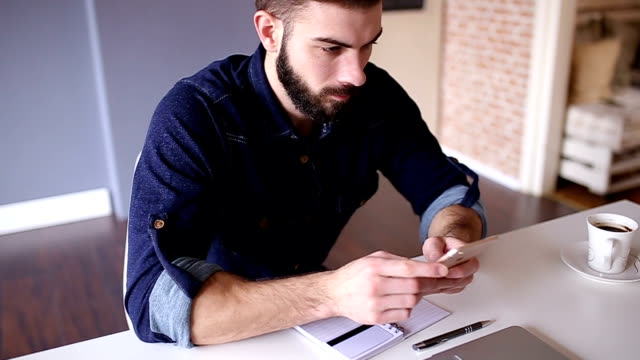 Handsome man using his phone in home office