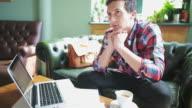 Stilig man använder laptop i kaféet.