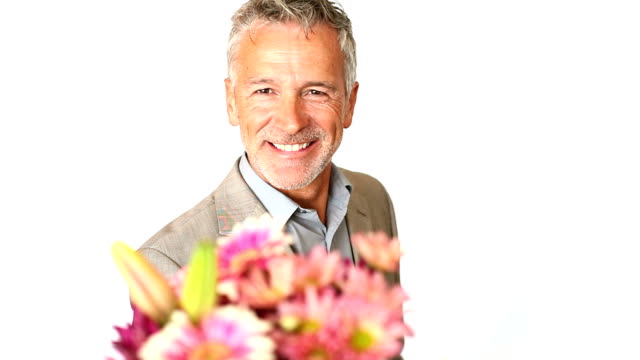 A handsome mature man holding flowers and presenting them to you isolated on white