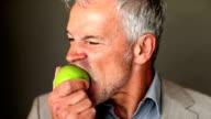 A handsome senior executive eating an apple on a dark background
