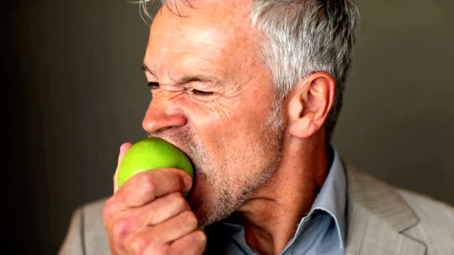 A handsome senior executive eating an apple on a dark background