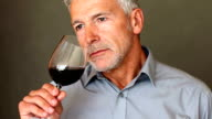 A handsome senior man smelling and then tasting a glass of red wine