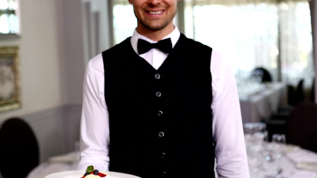 Handsome waiter showing dessert plates