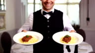 Handsome waiter showing spaghetti dinners