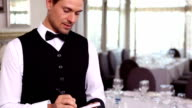 Handsome waiter taking an order