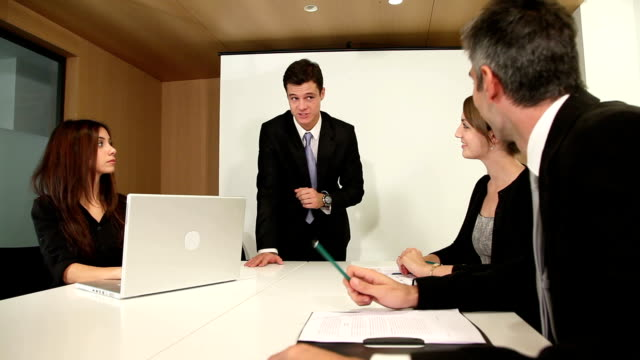 Handsome young business boss holds meeting with small group