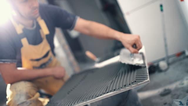 Handyman applying adhesive onto a ceramic tile.