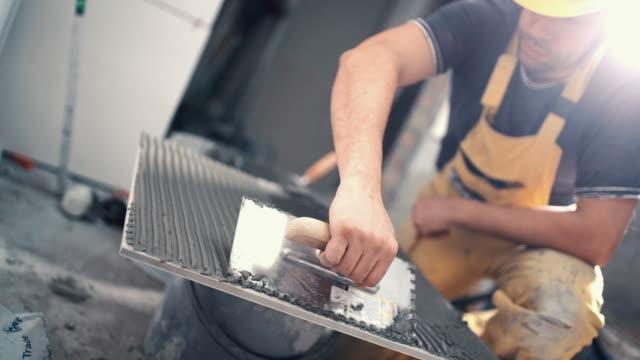 Handyman Kleberauftrag auf einer Fliese.