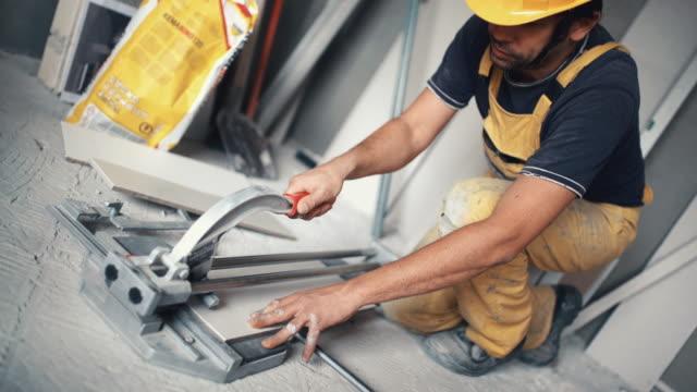 Handyman cutting ceramic tiles.