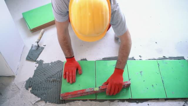 Handyman installing ceramic tiles.