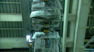 Hanging newspapers moving overhead on conveyor system ROTATE UNDER Moving papers TD WS Warehouse machines w/ elaborate conveyor system above...