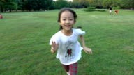 Happiness asian little girl running in the park
