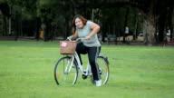Grasso Donna asiatica felice posa con bici all'aperto