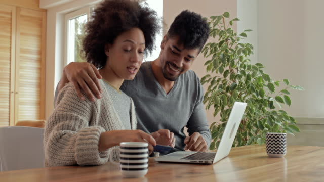 Happy African American couple communicating while shopping online from their home.