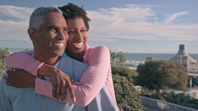 Gelukkig African American paar omarmen in de buurt van strand