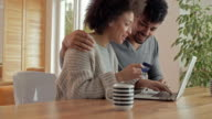 Happy African American couple shopping online on their laptop at home.