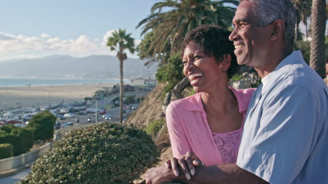 Happy African American Couple Talk on a Beach Boardwalk