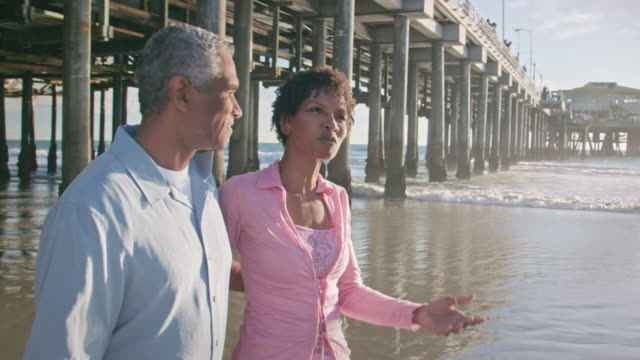 Happy African American Couple Walk and Talk Along the Beach