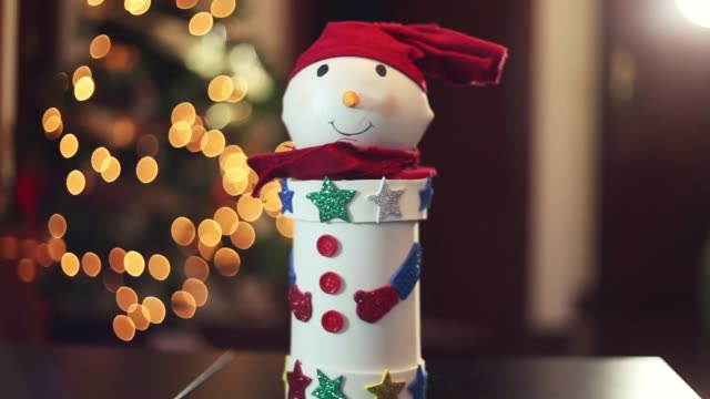 Happy and cute homemade snowman in front of the Christmas tree lights.