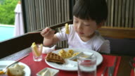Happy Asian boy eating breakfast at the Hotel.