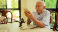Happy asian senior man using the mobile phone at home