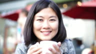 Happy Asian woman holding a cup of coffee, pavement cafe.