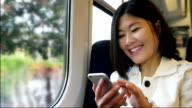 Happy Asian woman on a train using her mobile phone.