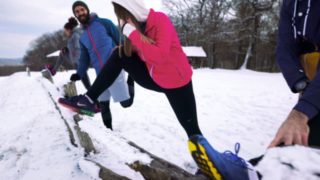 Happy athletic people exercising on the snow and doing stretching exercises.