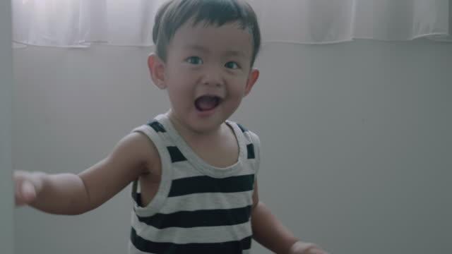 Glückliches Baby Boy spielen verstecken und suchen zu Hause