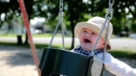 Happy Baby Boy Sitting in Playground Swing Outdoors with Mom