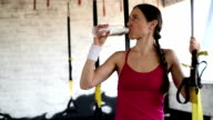 happy beautiful woman  drinks water. TRX straps.