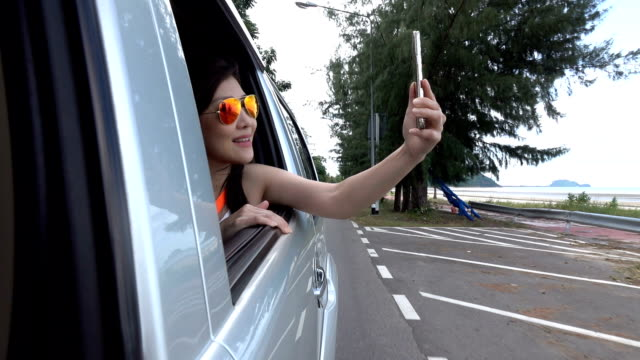 Happy beautiful Woman looking out the moving Car Window, feel free with sunny sea view