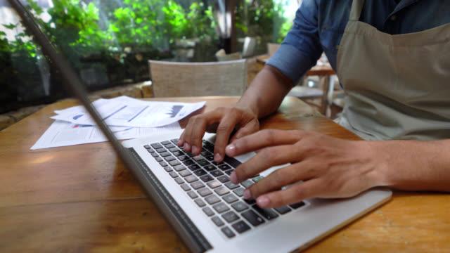 Glücklich schwarz Eigentümer von seinem Restaurant arbeiten auf einem Laptop und Notizen