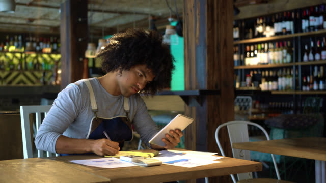 Happy black business owner of restaurant doing the books using a tablet and notepad