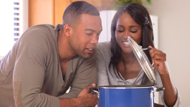 Happy black couple cooking in the kitchen