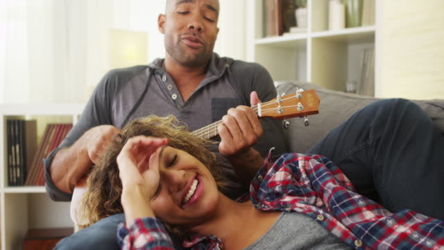 Happy black couple lying on couch with ukulele