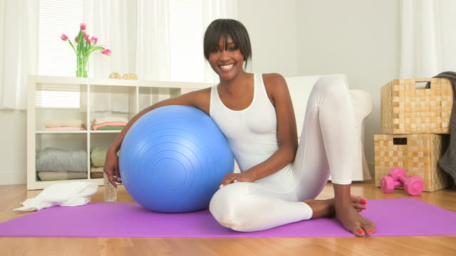 Happy black woman posing with exercise ball