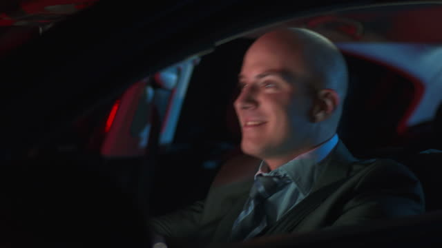 HD DOLLY: Happy Businessman Driving At Night