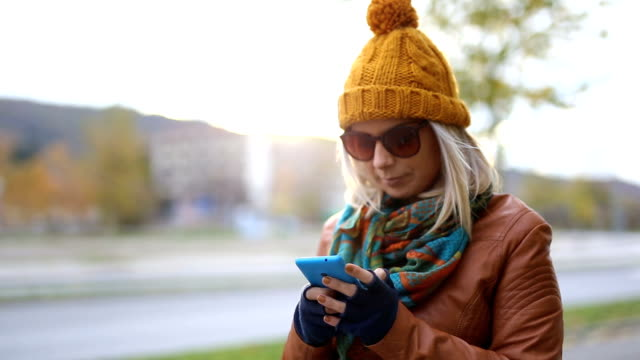 Happy charming blonde using smartphone in the city street