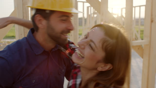 Happy couple architects hugging at construction site