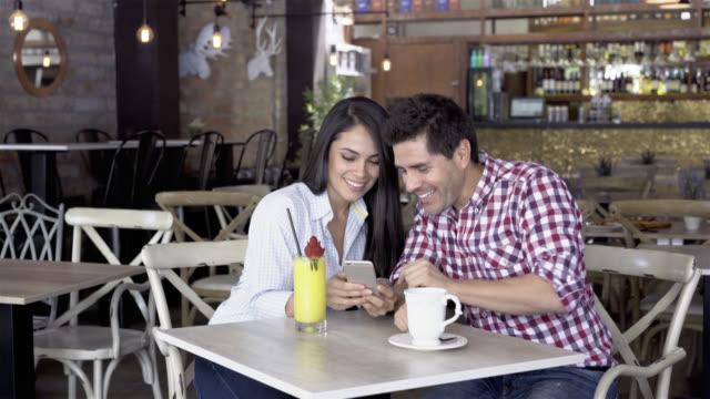 Gelukkige paar in een cafe sociale media kijken en lachen