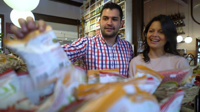 Glückliches Paar auf einem Gastronomie-Markt Auswahl Produkte zu kaufen, setzen sie in einen Korb