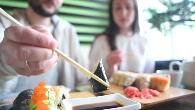 Happy couple eating sushi rolls in japan restaurant