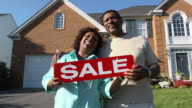 Happy Couple Holding SALE Sign