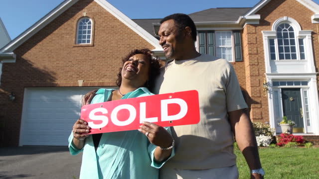 Happy Couple Holding SOLD Sign